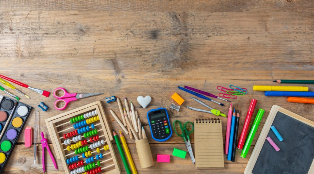 Back to school. School supplies on wooden background, top view