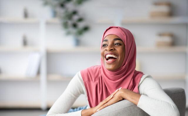 Joyful Laughing Black Muslim Woman In Hijab Sitting In Chair At Home