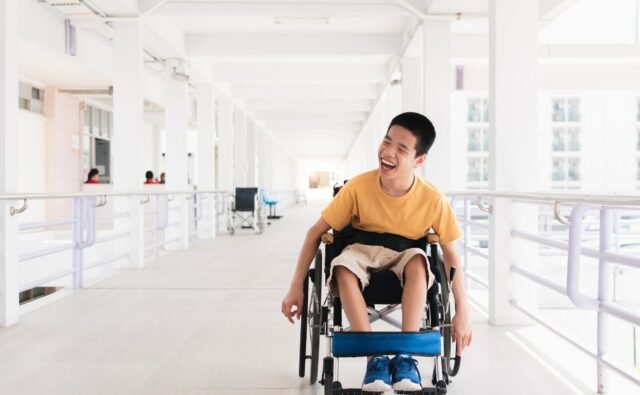 special child on wheelchair is smiling face as happiness on ramp for disabled people